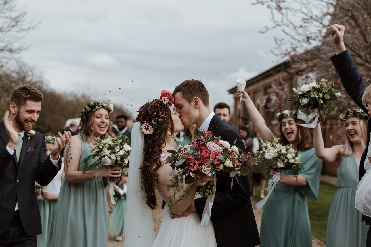 Bride and groom are showed in confetti as they kiss