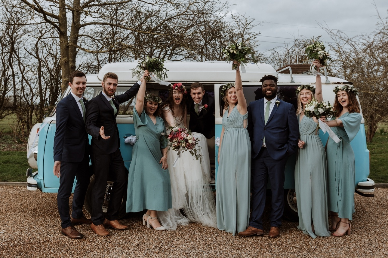 Bridal party celebrate in front of a blue VW campervan