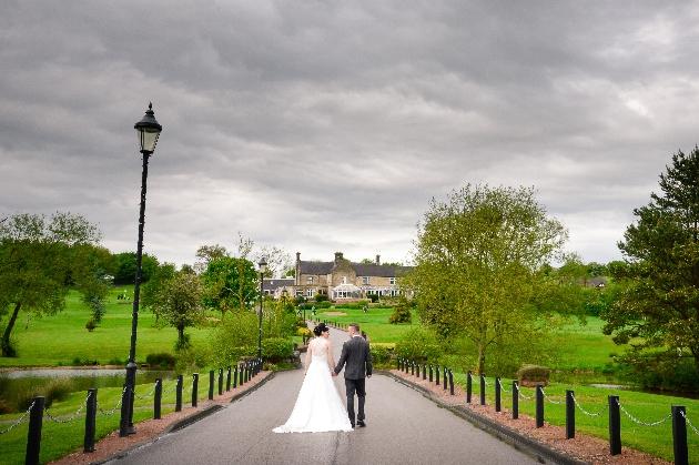 Couple walking down the beautiful driveway at Horsley Lodge