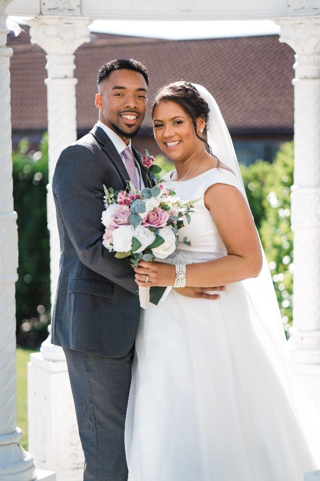 Newlyweds pose with bouquet
