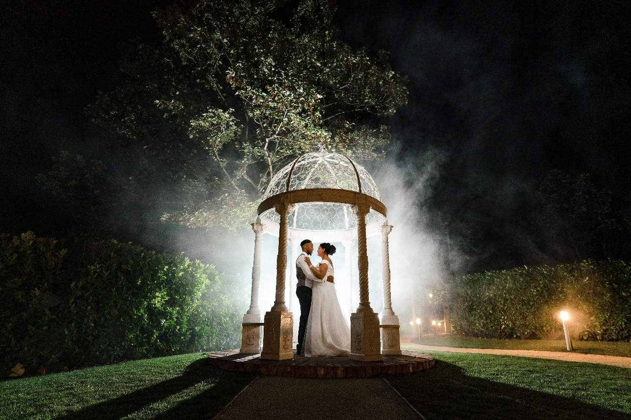 Bride and Groom pose in illuminated bandstand
