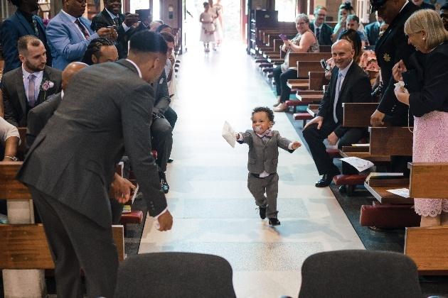 Toddler runs towards groom bearing rings