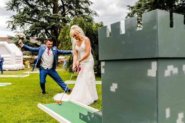 Bride and groom playing crazy golf at their wedding