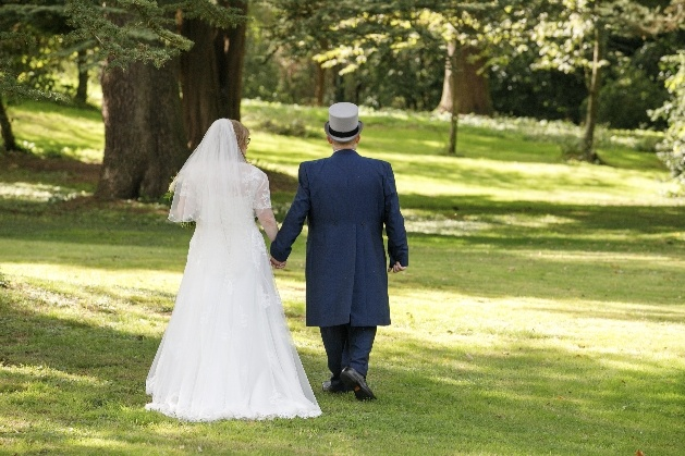 Bride and groom walk through grounds