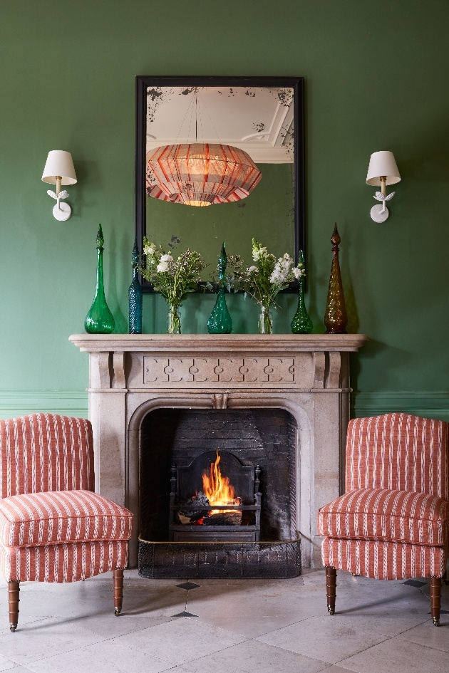 green wall fireplace two armchairs